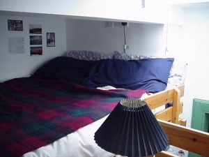Box room with double bed mattress on raised platform