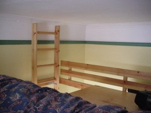 Smaller living / bedroom with double bed mattress on a raised platform
