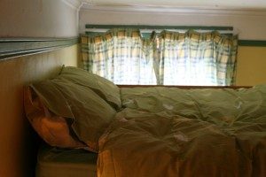 Double bed mattress on raised platform in smaller living / bedroom.