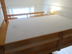 Double bed on platform above seating area in bedroom