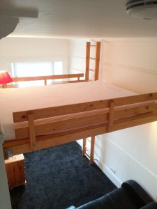 Double bed above seating area in bedroom