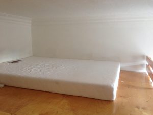 Double bed mattress on raised platform.